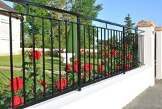 Black metal fence stands on white concrete base with large brick-topped gate surround.