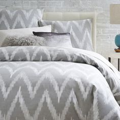NEW COLOR! This graphic, large-scale interpretation of a woven ikat pattern simplifies the traditional ethnic motif down to its most basic and clear shapes, printing it in a pale platinum on stone-white cotton.