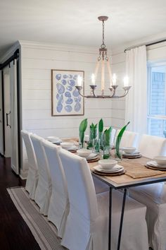Wood dining table, upholstered seating, pendant lighting, coastal design, abstract art