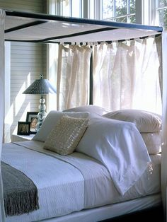 Off the great room, French doors open to an ethereal bedroom, bedecked in calming neutrals and luxurious fabrics. Above the stove-black, pencil-post bed, a ceiling fan circulates air, adding a seductive breeze that billows the fabric. The fan's durable resin blades, powder-coat finish, and stainless-steel hardware protect it from the damp coastal climate. (Photo: Photo: John O'Hagan)