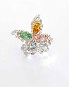 AN IMPORTANT COLOURED DIAMOND AND DIAMOND RING Double pavé-set circular-cut diamond  - diamond accents, circular-cut diamond and pink diamond butterfly, pear-shaped fancy intense yellowish green, fancy vivid yellowish orange, fancy pink and fancy light grayish blue diamond wings, weighing 2.01, 1.31, 1.07 and 1.01 carats, to the marquise-cut fancy orangy pink diamond body, weighing 0.27 carat, terminating in two pear-shaped diamonds, circular rose-cut swivel, can be worn on one or two…