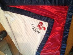 """Rocco """"Rocky"""" blanket in red white and blue (the American flag boxers rocky wore) Used fabric glue for the """"iron on"""" gloves and letters fire the name  There is NO boxing themed baby stuff anywhere!!! * I used fabric glue because I thought a hot iron might melt,distort or the patched wouldn't stick. I used a toothpick to trace fabric glue to letters*"""