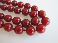 "Opaque Cherry Amber Bakelite Bead Necklace. Flapper Length 37"" Hand Knotted Silk Hidden Carved Screw Clasp C1930 by MercyMadge on Etsy"