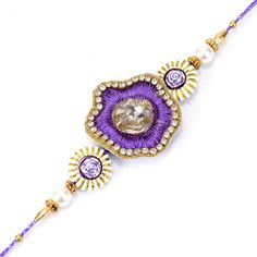 Delightful Violet Rakhi  This rakhi thread is extremely gorgeous as the center piece is decorated with violet colored stones. there are two floral designs on the side of the central piece. No matter wherever you are residing, you can make your beloved brother in India excited on the auspicious occasion of Rakhi by gifting this beautiful Rakhi thread through Giftblooms.com.