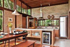 Sala e cozinha integradas ocupam o bloco social, fechado em grande parte com ...