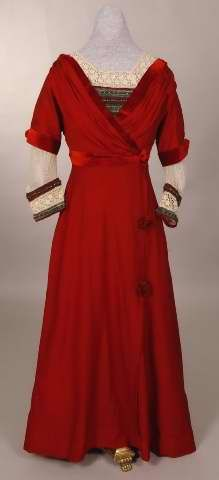 Red wool dress trimmed with red velvet and white lace, 1908-1912. The bodice, with a back closure, is draped and crosses in front like a loose jacket. It is edged with velvet that forms a rosette. A dicky of multi-colored beads with gold lace over red and turquoise. The oversleeves reach to the elbows, and wrist length undersleeves are of white lace. Cuffs of the beads similar to those on the dicky. The high waisted skirt flares slightly, and appears to open down the side, closes with…