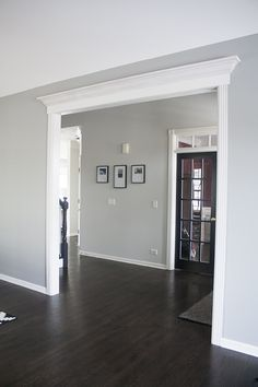 I LOVE the dark wood floors and the light grey walls/white trim. I also like how the entryway is framed and crown moulding added. Home makeover ideas! wood floors grey walls Home Tour Living Room Wood Floor, Living Room Grey, Living Room Decor, Living Rooms, Living Room Ideas With Dark Wood Floors, Revere Pewter Living Room, Living Room Hardwood Floors, Dining Room Paint, Bedroom Flooring