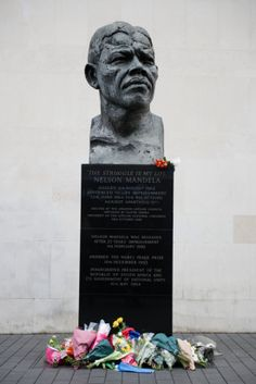 Bouquets sat at the base of a Nelson Mandela bust in London..