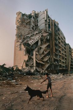 Boy walking his dog near a destroyed building | Lebanon. This photo shows how a boy is walking his dog near a very badly destroyed building which was probably cause by a bomb. i feel as it shows that everyday life can be destroyed somehow but you can always ignore it and walk around as shown the boy doesn't really care about the building and is still going on with his life.