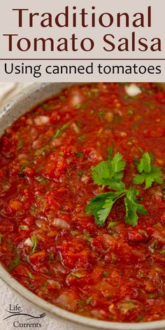 a large bowl of tomato salsa garnished with cilantro leaves, title on top: Traditional Salsa Recipe using canned tomatoes.