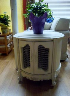 Vintage end table that we painted (antique white) and distressed for a shabby chic look. Very country cute with it's original hardware and chicken wire doors.