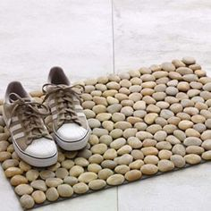 Each doormat is created by hand using river rocks that are washed and polished and then affixed to plastic netting.