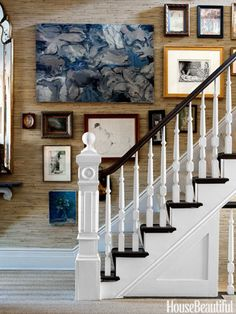 Grass cloth wallpaper with crisp blues and whites in this stair hall give this home a modern traditional beach vibe.