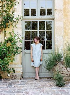I love EVERYthing about this picture. The door, the plants, the pastels, her dress, her pose. I'd love to find a good door.