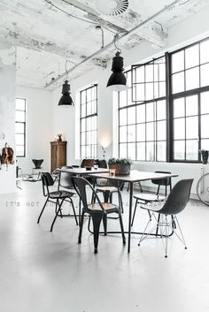 White interior, loft space, metallic lamps, open glass window, table, wooden drawer