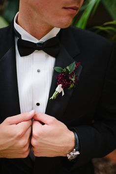 the groom in a classic black tuxedo wears his boutonniere of burgundy scabiosa, astilbe and seeded eucalyptus.