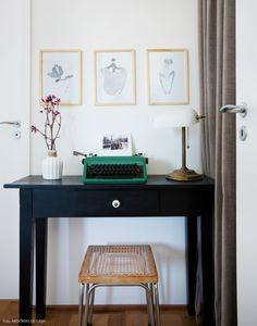 Entrada do quarto de casal com escrivaninha preta e máquina de escrever.