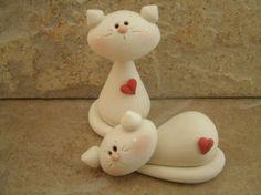 Ein paar süße Kätzchen aus weißem fimo erstellt. Jede ziert mit einem winzigen roten Herz.  Dies ist ein original-Design, das handgefertigt worden ist. Die sitzende Kitty steht knapp 2 groß... die ruhelosigkeit Kitty ist knapp 2 lang. Alle Teile wurden mit flüssigem Polymer für erhöhte Stärke gesichert und beide Stücke haben mit einer Matt Glasur leicht verglast worden.  Kein Spielzeug... nicht für Kleinkinder geeignet.