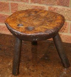 A delightful small elm milking stool.  The burr top with three ash legs all secured with a peg to the top.  The underneath with a dish stamped DP in 13 places.