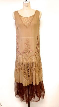 1920s Silk Chiffon Silk Embroidered Lace Flapper Dress. Majority of the dress is constructed out of light brown silk chiffon. The bodice of the dress has incredible sick silk embroidery. The drop waist is scalloped with braided cording in the same material. Below this piece is monochromatic floral lace. The next tier is the same silk chiffon with brown netting underneath. Front
