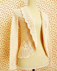 This is an open front cardigan, with rounded hem at front, featuring pineapple patterns against a background of plain double crochet sts at lower part of the cardigan. The back, front and arms are worked from bottom up, ending with raglan shaping in a fan pattern. Then you finish off with a shawl collar around back and front piece in fan patterns as well.