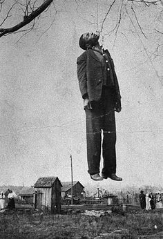 In this picture a man is hanging from a tree. This is known as lynching as it says in the book. The white men in groups would hang the colored men as a punishment even if they didn't have a legal trial. This was common during 1954-1968 and is a form of discrimination.