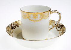 kopp med fat 1756. Cylindrisk kopp. Mjukt porslin. Dekor rocailleranka i guld mot vitt.
