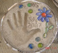 See a picture of a home-made garden stepping stone submitted by Jennifer Super. It features a handprint design along with glass bead embellishments.
