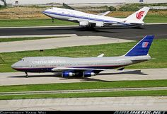 Air China Boeing 747-400 taking off and United Airlines Boeing 747-400 taxiing at Beijing Airport in 2007.