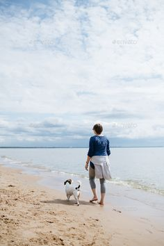 Woman walking with her dog on the sandy beach. Rear view. - Stock Photo - Images