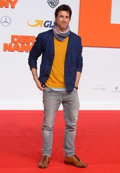 """Gala Men: Für die Berlin-Premiere von """"Der Nanny"""" wird das Styling von Florian David Fitz ganz frühlingshaft. Den gelben Strickpulli zur grauen Jeans kombiniert er mit blauem Baumwoll-Blazer und schickem Halstuch."""