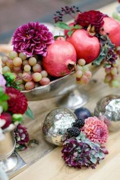 12 Yummy-Looking Wedding Centerpieces With Fruits And Vegetables: a silver bowl with grapes, pomegranates and burgundy dahlias for a fall wedding