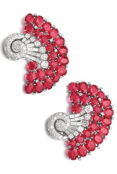 Seaman Schepps - A pair of Art Deco synthetic ruby and diamond clips, 1930s. Each of scroll design, set with circular-cut and oval synthetic rubies, and circular-, single-cut and baguette diamonds, signed Seaman Schepps. #SeamanSchepps #ArtDeco #clip