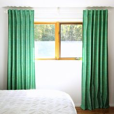 Green tweed DIY back tab curtains - shot with aqua! - look perfect with the mid-century art in this bedroom.