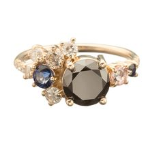 Vega Cluster Ring from the Unexpected Unions collection. Center black diamond ranges in weight from 1.45ct - 1.55ct. Imperial topaz weighs approximately .14 ct. 2 Blue Sapphires range in weight from .05ct - .23ct. 3 Diamonds weigh approximately .16ct in total. 2 Champagne Diamonds weigh approximately .14ct in total. 6 Pave set White Diamonds weigh approximately .05ct in total. 1.7mm round wire shank. If you're interested visit the store, email mociun@mociun.com or call 7183873731
