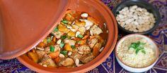 Een heerlijk Marokkaans gerecht met kip, wortel, amandelen en zoete abrikozen bereid in een Tajine