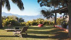 Forrado de grama são-carlos (Odara Jardins), o jardim convida a ler sob as árvores. Poltrona de cipó trazida do Ceará e pufe de cordas de polipropileno (Tidelli).