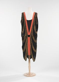 This dress is a perfect representation of the flapper era of the 1920s. Breaking free from the confining dresses of days past, the chest was flattened, the waist was dropped and the hemline was raised. The construction is ingenious, as it accommodates the pattern of the textile and drapes with the configuration of the scallop pattern.