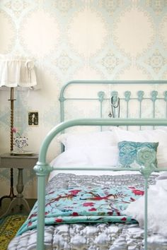 Antique iron bed painted robin's egg blue to match beautiful wallpaper.