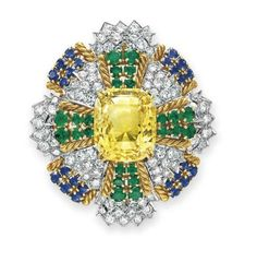 A DIAMOND, YELLOW SAPPHIRE, EMERALD AND SAPPHIRE BROOCH, BY DAVID WEBB Set with a detachable cushion-cut yellow sapphire, within a two-tiered circular-cut diamond, emerald and sapphire surround with sculpted gold detail, mounted in gold and platinum, with pendant hook for suspension, circa 1965.