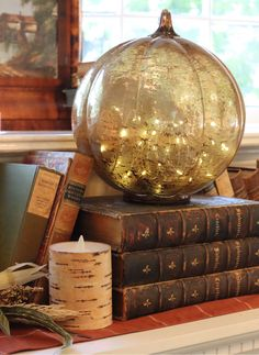 We're completely spellbound by Lauren Nicholsen's indoor display of Glowing Glass Pumpkins and seemingly magical books. Perfect for a subtle and elegant Halloween display.