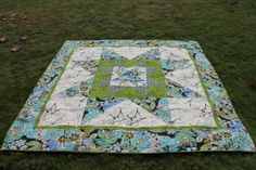 """This quilt is filled with old fashion appeal but with a contemporary twist. The fabrics are colorful and reminiscent of bright and bold african prints. In the center of the quilt is a beautiful star within a star within a star which will look lovely on a bed. The wide floral border frames the quilt beautifully.  This quilt measures 82"""" x 86"""""""