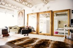 A trio of gilded, oversized mirrors visually doubles the size of this space reflecting the open, uncluttered home. Lofty ceilings further help enlarge the home, while a variety of rugs define...