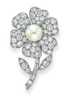 A DIAMOND AND CULTURED PEARL FLOWER BROOCH, BY VAN CLEEF & ARPELS Designed as a circular-cut diamond flower with a cultured pearl pistil, measuring approximately 9.60 mm, to the baguette-cut diamond stem and circular-cut diamond leaves, mounted in platinum