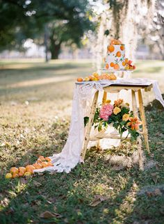 Hand-Painted Wedding Cake with Orange Citrus Cake Topper on Vintage and Lace Table   Tampa Bay Rentals by Tufted Vintage Rentals