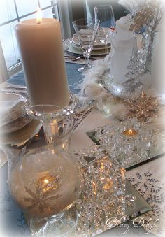White candles on mirror tiles complete a white Christmas table setting