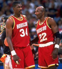 Clyde Drexler and Hakeem Olajuwon talk on the court during Game...