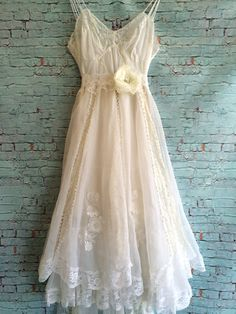 One of a kind. The top of this dress is white nylon with chiffon overlay, lace appliqué, and triple spaghetti straps. The skirt has three