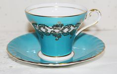 Aynsley Bone China Teacup & Saucer  It is in the Corset Shape Dark Turquoise Color with wide White Band Overlayed with Gold Gild Scrolls  There are no cracks or chips There are some tiny paints flecks on the saucer