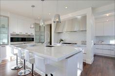 Cozinha branca com piso escuro e pedra no acabamento.
